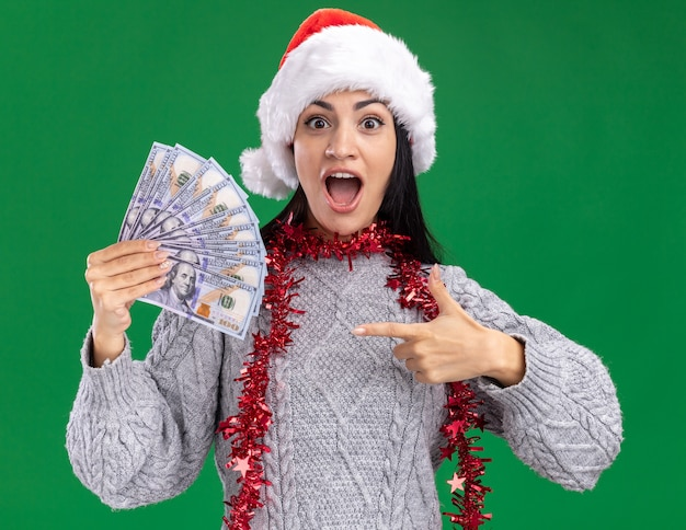 Impressed young caucasian girl wearing christmas hat and tinsel garland around neck holding and pointing at money looking at camera isolated on green background