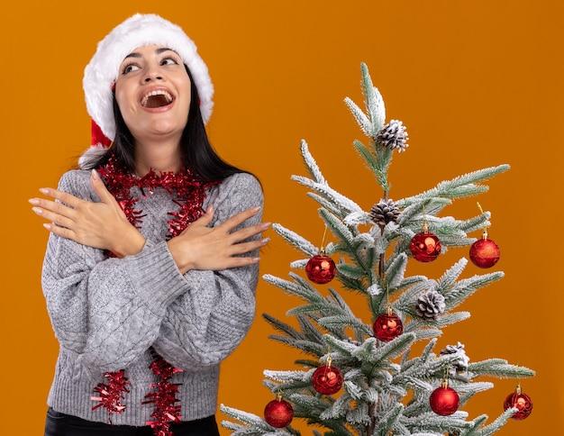 Impressionato giovane ragazza caucasica indossando il cappello di natale e la ghirlanda di orpelli intorno al collo in piedi vicino all'albero di natale decorato tenendo le mani incrociate sulle braccia alzando lo sguardo isolato su sfondo arancione