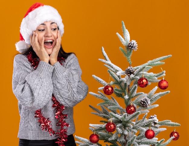 Impressionato giovane ragazza caucasica che indossa il cappello di natale e la ghirlanda di orpelli intorno al collo in piedi vicino all'albero di natale decorato tenendo le mani sul viso guardando in basso isolato sul muro arancione
