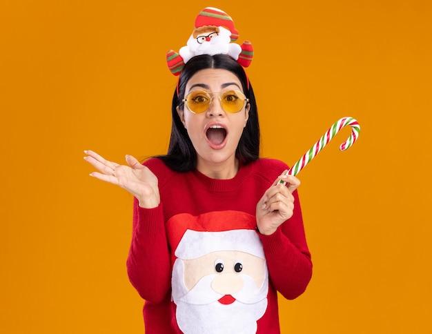 オレンジ色の背景で隔離の空の手を示すカメラを見て伝統的なクリスマスのキャンディケインを保持しているメガネとサンタクロースのヘッドバンドとセーターを着ている感動の若い白人の女の子