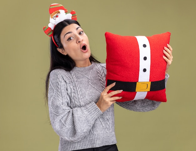 Impressed young caucasian girl wearing santa claus headband holding santa claus pillow looking at camera isolated on olive green background