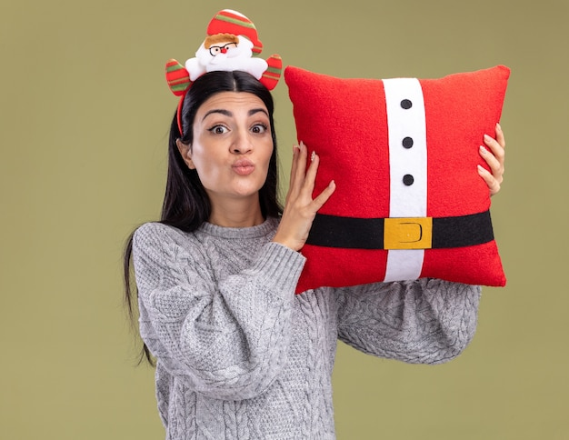 Impressed young caucasian girl wearing santa claus headband holding santa claus pillow near head pursing lips looking at camera isolated on olive green background