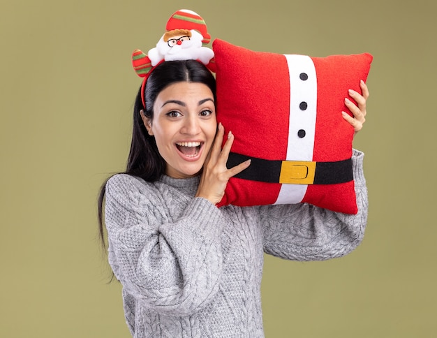 Impressed young caucasian girl wearing santa claus headband holding santa claus pillow touching head with it looking at camera isolated on olive green background