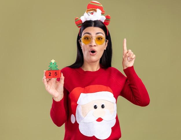 Impressionato giovane ragazza caucasica che indossa la fascia di babbo natale e maglione con gli occhiali che tiene il giocattolo dell'albero di natale con la data che guarda l'obbiettivo rivolto verso l'alto isolato su sfondo verde oliva
