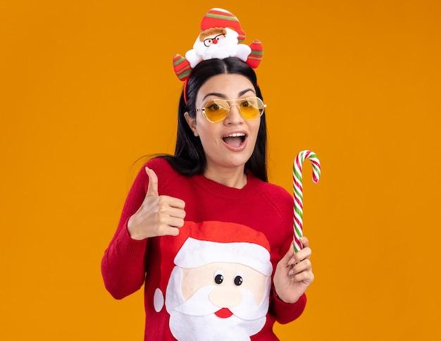 Impressionato giovane ragazza caucasica che indossa la fascia di babbo natale e un maglione con gli occhiali che tengono il tradizionale bastoncino di zucchero natalizio che mostra il pollice in alto isolato sulla parete arancione con spazio di copia