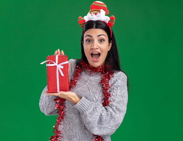Impressed young caucasian girl wearing santa claus headband and tinsel garland around neck holding gift package looking at camera isolated on green background