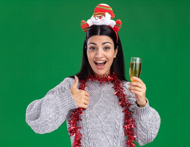 Impressed young caucasian girl wearing santa claus headband and tinsel garland around neck holding glass of champagne looking at camera showing thumb up isolated on green background