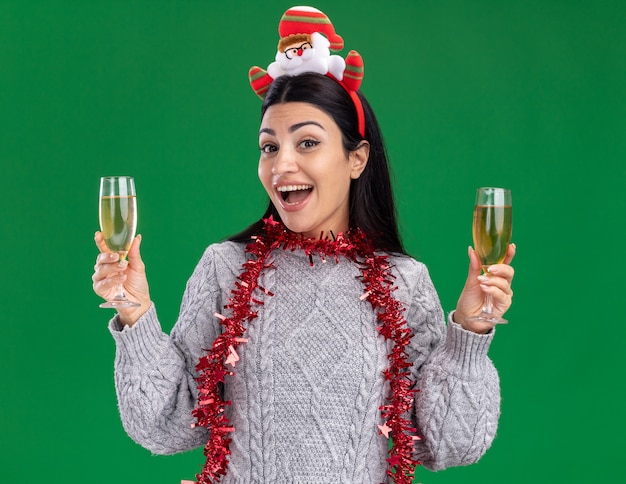Impressed young caucasian girl wearing santa claus headband and tinsel garland around neck holding two glasses of champagne looking at camera isolated on green background