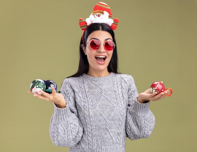 Impressionato giovane ragazza caucasica indossando la fascia di babbo natale con gli occhiali che tengono le bagattelle di natale che guarda l'obbiettivo isolato su sfondo verde oliva