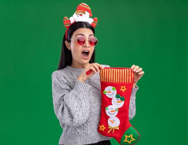 緑の背景に分離されたカメラを見てクリスマスの靴下を保持しているメガネとサンタクロースのヘッドバンドを身に着けている印象的な若い白人の女の子