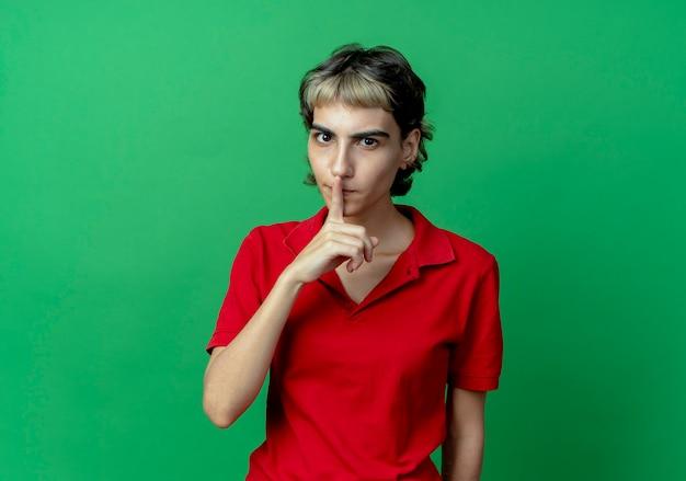 コピースペースで緑の背景に分離されたカメラで沈黙を身振りで示すピクシーの散髪を持つ印象的な若い白人の女の子