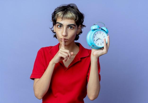 Впечатленная молодая кавказская девушка с прической пикси держит будильник, жестикулируя тишину, изолированную на фиолетовом фоне с копией пространства