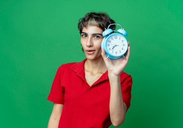 Впечатленная молодая кавказская девушка со стрижкой пикси держит будильник на зеленом фоне с копией пространства