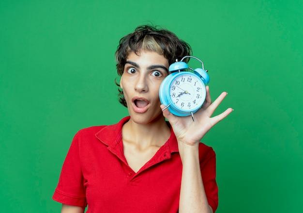 Впечатленная молодая кавказская девушка со стрижкой пикси держит будильник на зеленом фоне