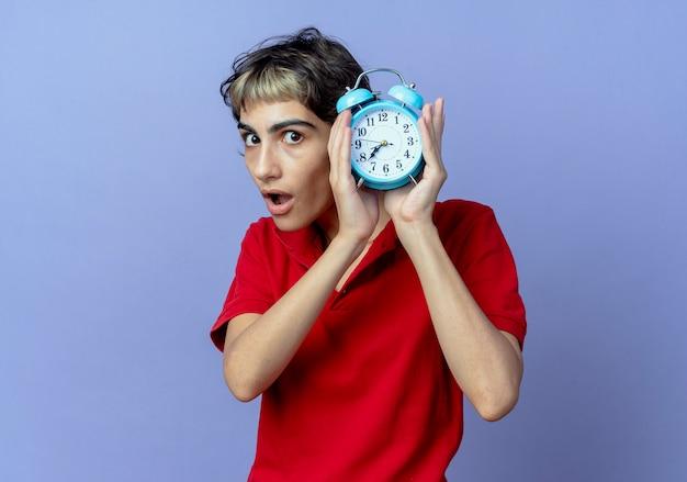 Впечатленная молодая кавказская девушка с прической пикси держит будильник на фиолетовом фоне с копией пространства