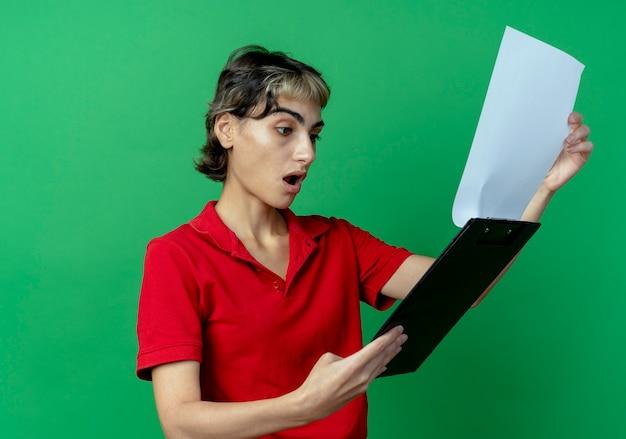 녹색 배경에 고립 된 클립 보드를 들고 픽시 머리를보고 감동 어린 백인 소녀
