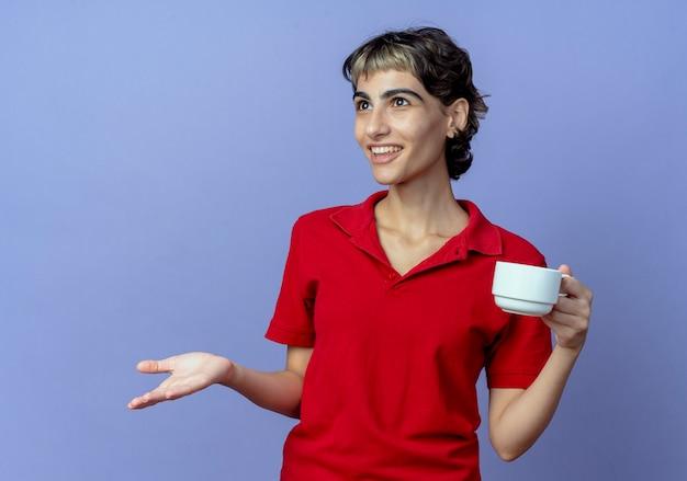 똑바로보고 보라색 배경에 고립 된 빈 손을 보여주는 픽시 헤어 스타일 들고 컵 감동 된 젊은 백인 여자