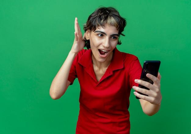 Impressionata giovane ragazza caucasica con un taglio di capelli da folletto che tiene e guarda il telefono cellulare e tiene la mano in aria