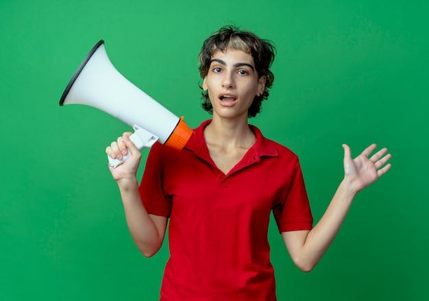スピーカーを保持し、緑の背景に分離された空の手を示すピクシーヘアカットと感銘を受けた若い白人の女の子