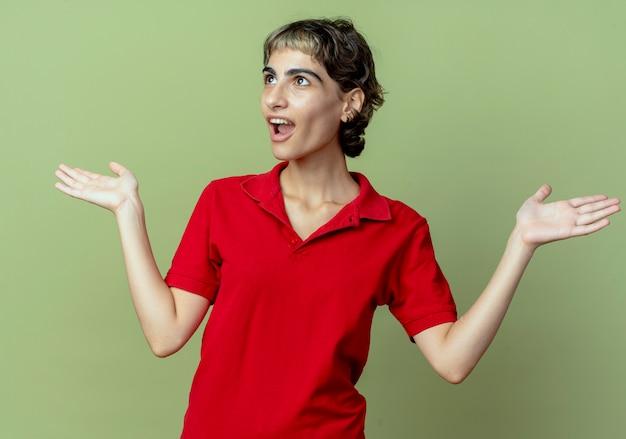 픽시 머리 측면을보고 올리브 녹색 배경에 고립 된 빈 손을 보여주는 감동 젊은 백인 여자