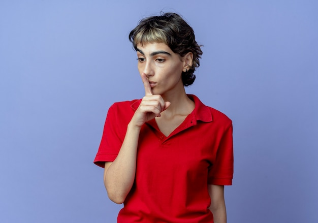 Impressed young caucasian girl with pixie haircut looking down and gesturing silence isolated on purple background with copy space