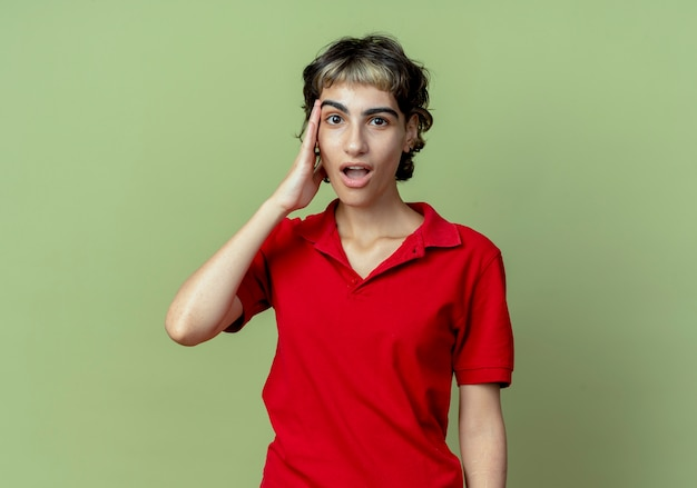 Impressionato giovane ragazza caucasica con taglio di capelli pixie mettendo la mano sul tempio isolato su sfondo verde oliva con lo spazio della copia