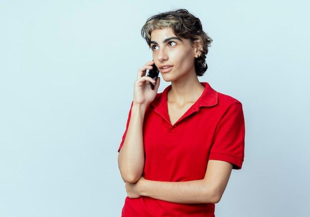 コピースペースと白い背景で隔離の腎臓に手でまっすぐに見ている電話で話しているピクシーヘアカットと感銘を受けた若い白人の女の子