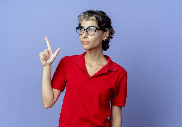 측면을보고 복사 공간이 보라색 배경에 고립 된 손가락을 올리는 안경을 쓰고 픽시 헤어 스타일로 감동 된 젊은 백인 여자