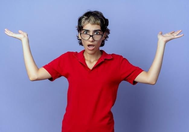 紫色の背景に分離された空の手を示す眼鏡をかけてピクシーヘアカットと感銘を受けた若い白人の女の子