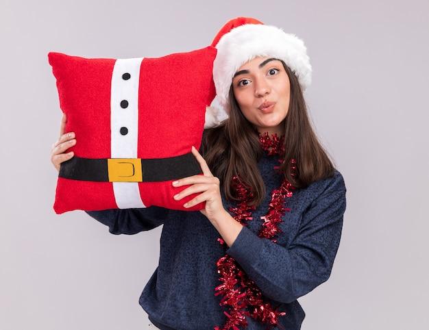 Impressionato giovane ragazza caucasica con santa cappello e ghirlanda intorno al collo tiene cuscino decorato isolato su sfondo bianco con spazio di copia
