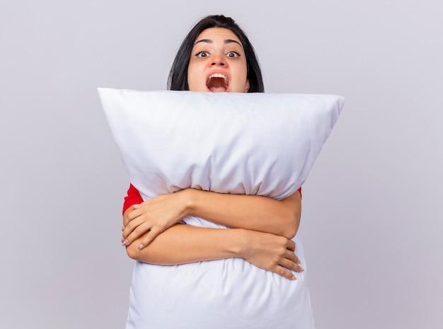 コピースペースと白い背景で隔離の後ろからカメラを見て枕を抱き締める印象的な若い白人の病気の女の子