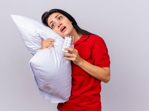 Impressionato giovane indoeuropea ragazza malata abbracciando cuscino mettendo la testa su di esso guardando dritto con confezione di compresse e bicchiere d'acqua in mano isolato su sfondo bianco con spazio di copia