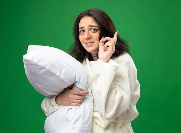 Впечатленная молодая кавказская больная девушка в халате, стоящая в профиль и обнимающая подушку, глядя в камеру, указывая вверх, изолированную на зеленом фоне с копией пространства