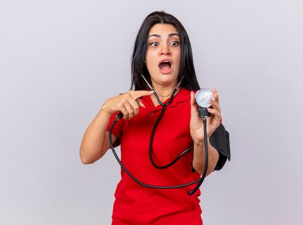 Впечатленная молодая кавказская больная девушка со стетоскопом, измеряющая ее давление с помощью сфигмоманометра, смотрит и указывает на него на белом фоне с копией пространства