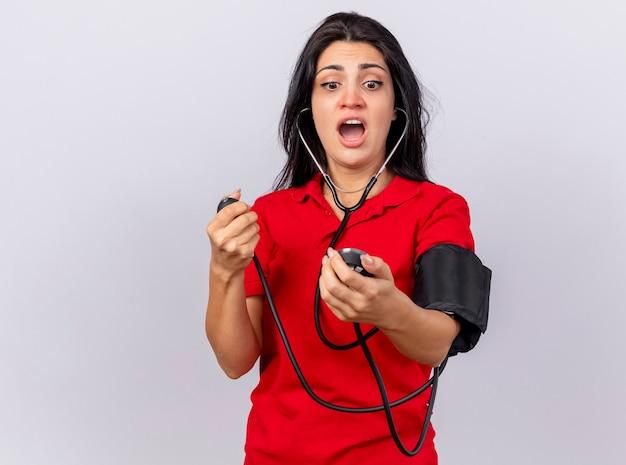 Впечатленная молодая кавказская больная девушка со стетоскопом, измеряющая давление с помощью сфигмоманометра, глядя на него на белом фоне с копией пространства