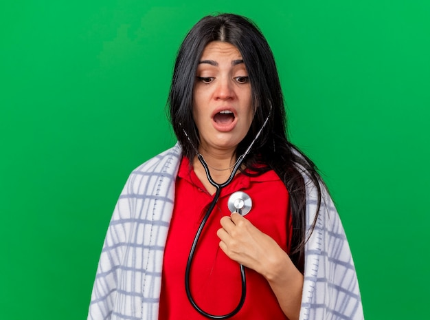 コピースペースで緑の背景に孤立して見下ろしている彼女の心拍を聞いて格子縞に包まれた聴診器を身に着けている感銘を受けた若い白人の病気の女の子