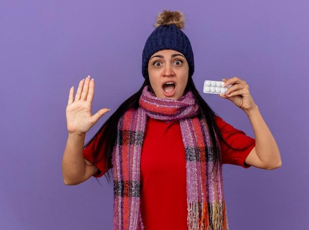 Впечатленная молодая кавказская больная девушка в зимней шапке и шарфе показывает пачку таблеток, глядя в камеру, показывая пустую руку, изолированную на фиолетовом фоне