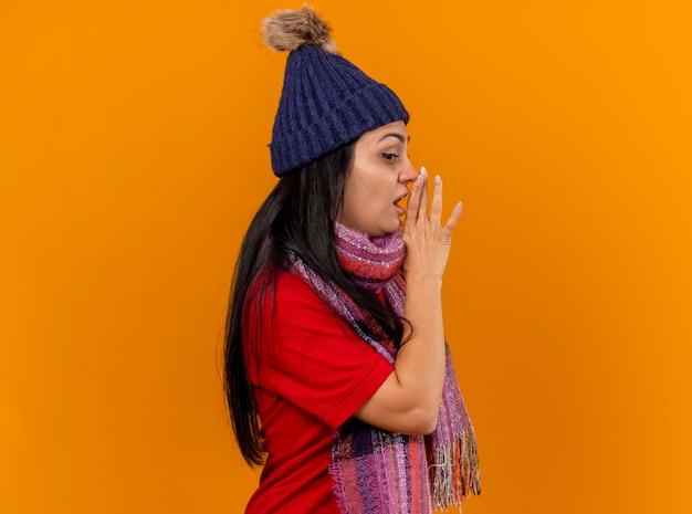 복사 공간 오렌지 벽에 고립 속삭이는 측면을보고 입 근처에 손을 유지 프로필보기에 서있는 겨울 모자와 스카프를 입고 감동 젊은 백인 아픈 소녀
