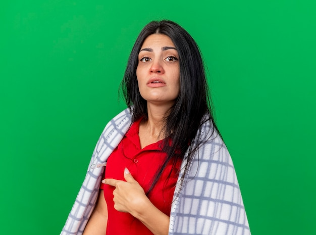 Impressionato giovane ragazza malata caucasica avvolta in un plaid che punta dietro isolato sulla parete verde con lo spazio della copia