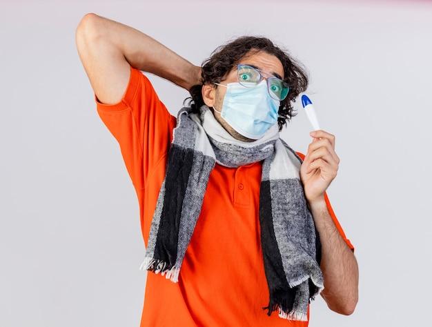 眼鏡とマスクを身に着けている印象的な若い白人の病気の人は、白い背景で隔離の頭の後ろに手を保つカメラを見て温度計を保持しています
