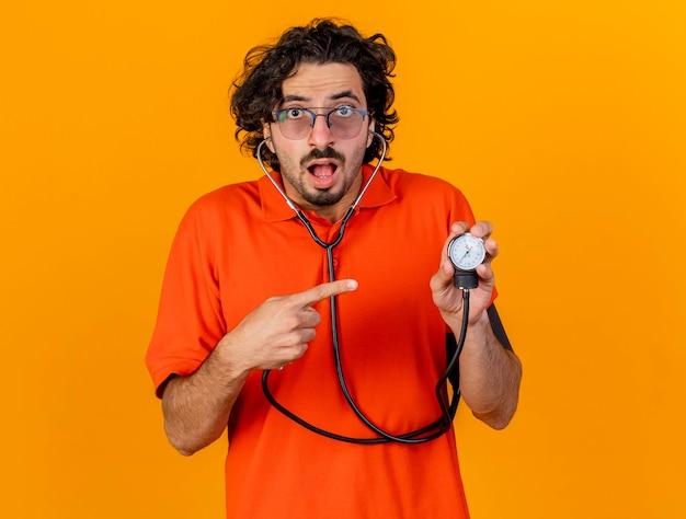 コピースペースとオレンジ色の壁に分離された血圧計を保持し、指している眼鏡と聴診器を身に着けている感銘を受けた若い白人の病気の男