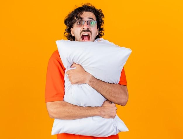 コピースペースでオレンジ色の背景に分離されたカメラを見て枕を保持している眼鏡をかけている印象的な若い白人の病気の男
