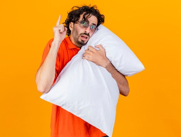 Impressionato giovane indoeuropeo uomo malato con gli occhiali che abbraccia cuscino guardando la telecamera alzando il dito isolato su sfondo arancione con spazio di copia