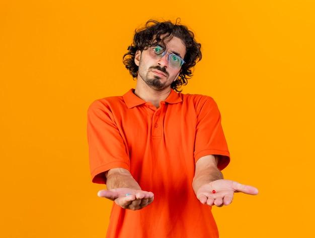 Impressionato giovane uomo malato caucasico con gli occhiali che guarda l'obbiettivo allungando capsule mediche verso la telecamera isolata su sfondo arancione con spazio di copia