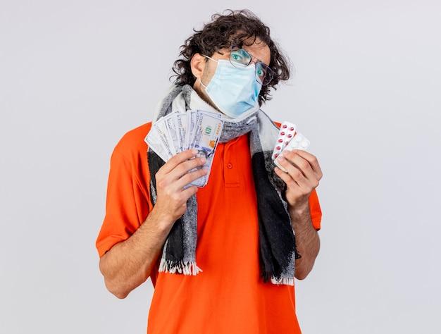 コピースペースと白い背景で隔離のカメラを見てお金と錠剤のパックを保持している眼鏡マスクとスカーフを身に着けている感銘を受けた若い白人の病気の男
