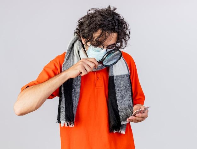 Impressionato giovane indoeuropeo uomo malato con gli occhiali sciarpa e maschera tenendo pillole mediche guardandoli attraverso la lente di ingrandimento isolati su sfondo bianco con spazio di copia