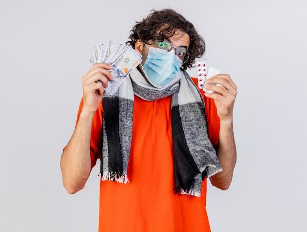 Impressionato giovane indoeuropeo uomo malato con gli occhiali sciarpa e maschera in possesso di denaro e pillole che guarda l'obbiettivo isolato su priorità bassa bianca