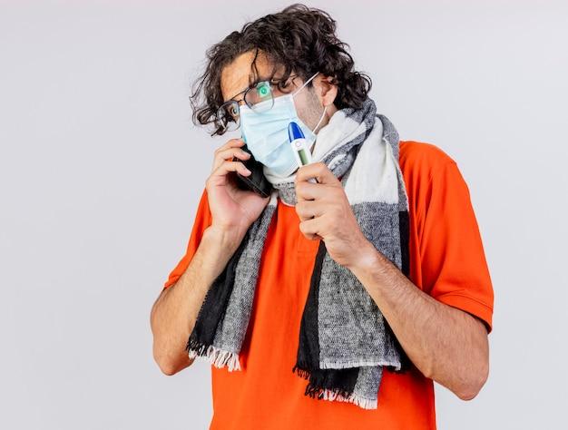 Impressionato giovane indoeuropeo uomo malato con gli occhiali sciarpa e maschera che tiene termometro guardando dritto parlando al telefono isolato sul muro bianco con lo spazio della copia