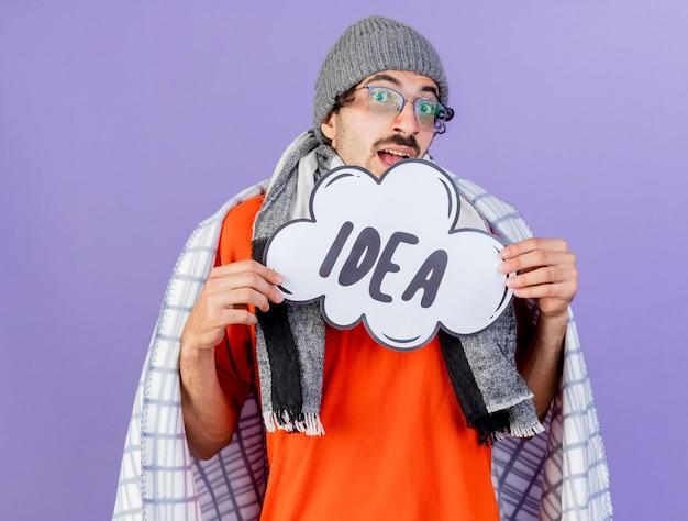 보라색 배경에 고립 된 카메라를보고 생각 거품을 들고 격자 무늬에 싸여 안경 겨울 모자와 스카프를 착용하는 감동 된 젊은 백인 아픈 남자
