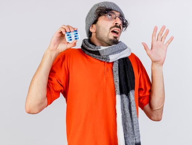 Impressionato giovane uomo malato caucasico con gli occhiali cappello invernale e sciarpa che tiene il pacchetto di capsule mediche alzando lo sguardo mostrando la mano vuota isolata sul muro bianco